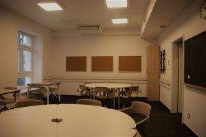 sala z krzesłami, stołami, ekranem i tablicą