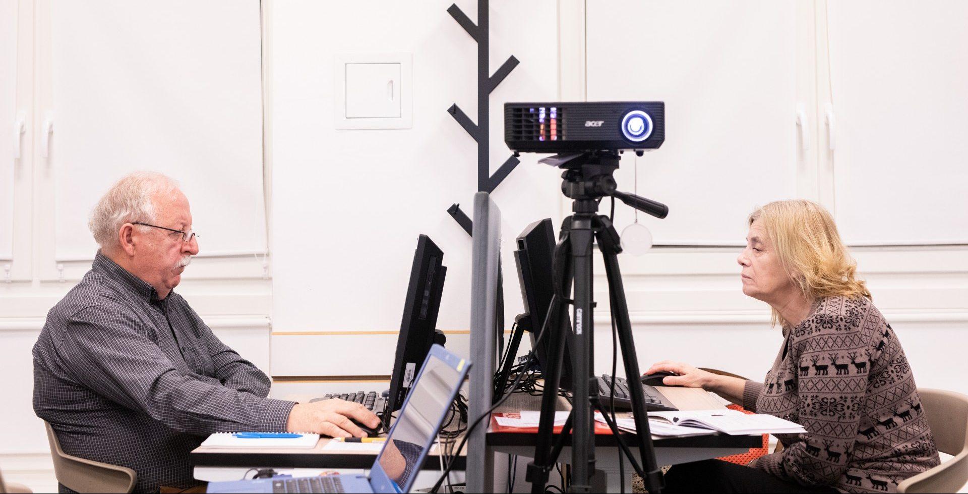 Na zdjeciu widać dwie osoby, patrzące w monitory komputerów, siedzące naprzeciwko siebie. Na pierwszym planie, widać rzutnik na statywie.