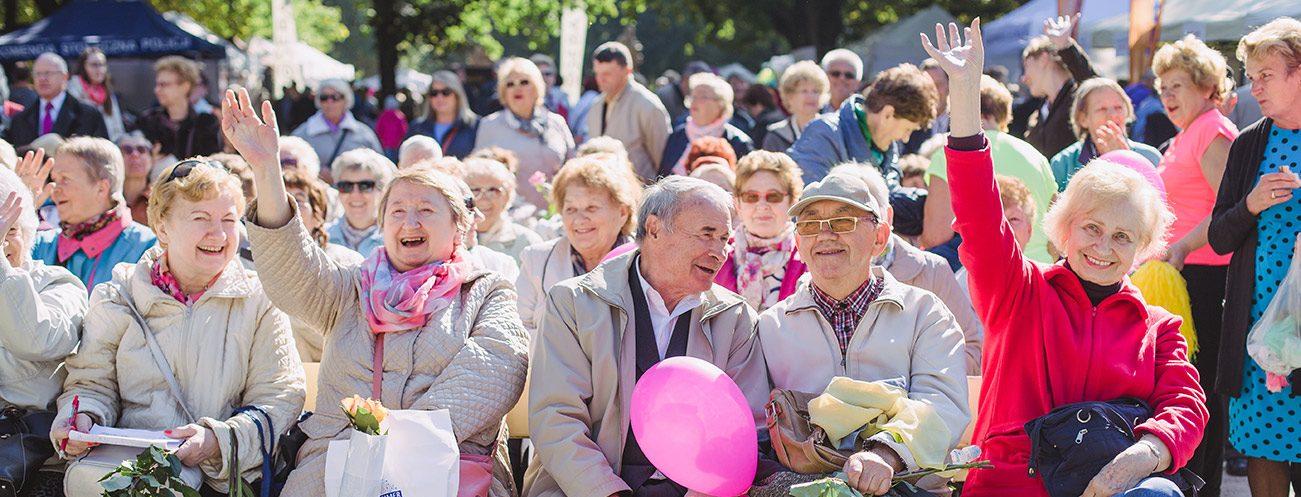 grupa osób starszych siedząca na ławkach i machająca w stronę obiektywu