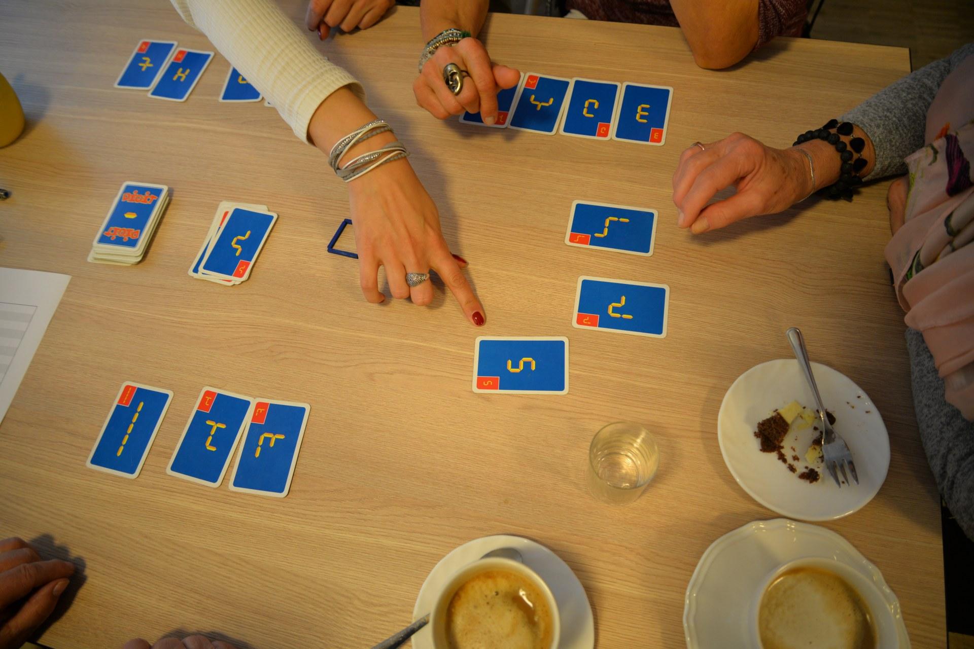 Na drewinianym stole rozłożone są w kilku miejscach karty w kolorze niebieskim, widać ręce graczy i filiżanki.