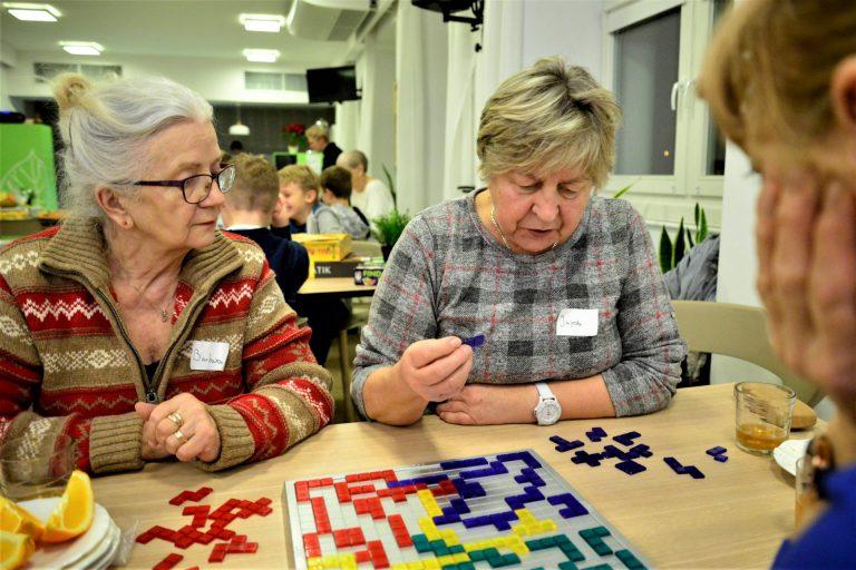 Trzy kobiety grają w grę planszową, układając małe kolorowe pionki.