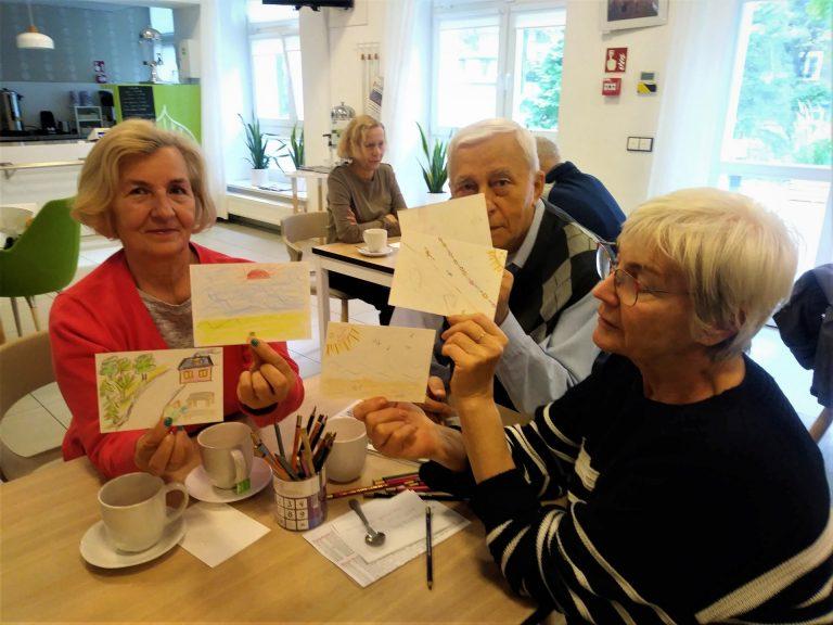 Trzy osoby siedzą przy stoliku i pokazują w stronę obiektywu przygotowane przez siebie kartki ze wspomnieniami.