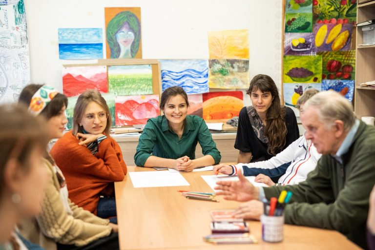 Uczestnicy projektu: młodzież i seniorzy siedzą wspólnie przy stole w trakcie warsztatów grupy twórczej.