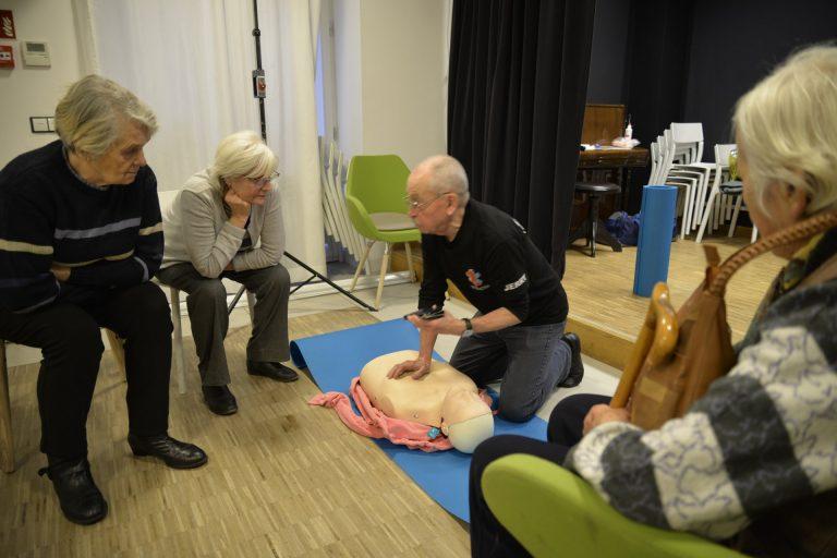 Grupa osób obserwuje instruktora pokazującego na fantomie ułożenie rąk to masażu serca.