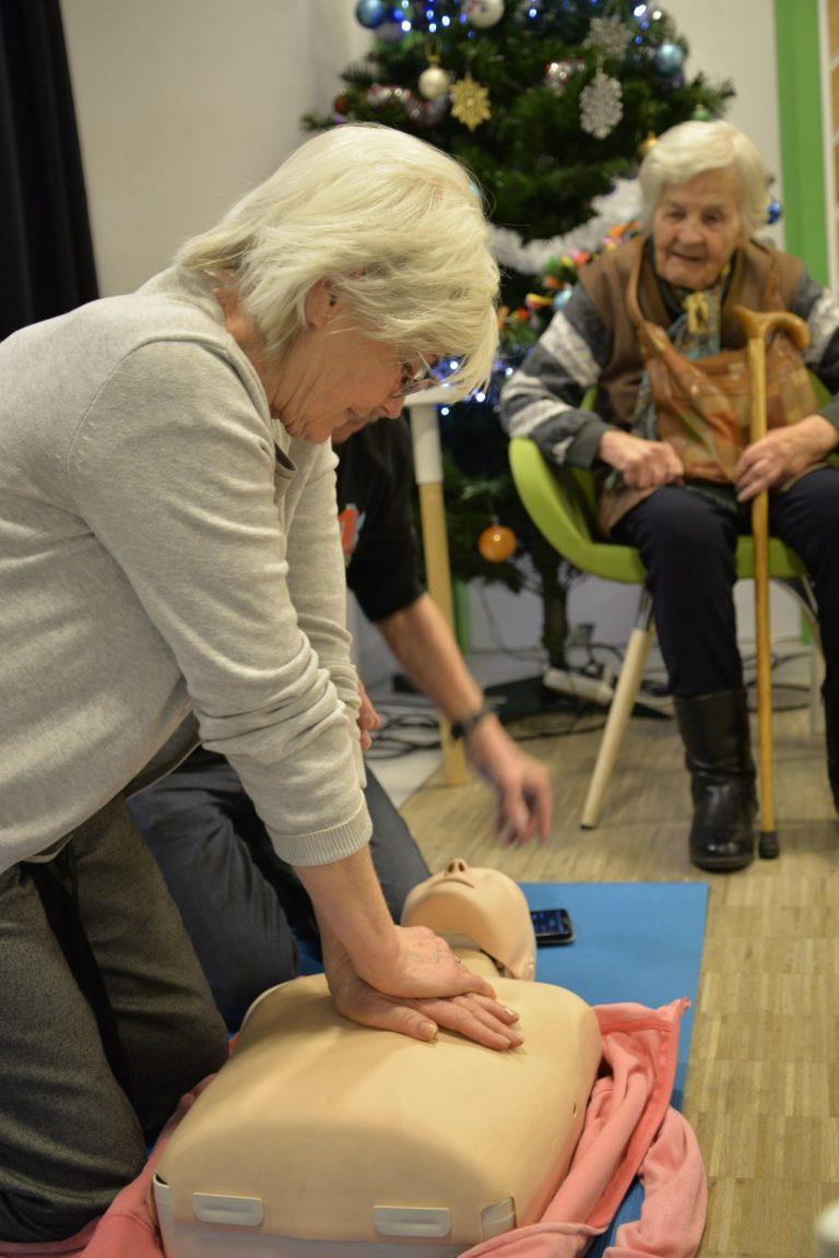 Starsza kobieta ćwiczy na manekinie ułożonym na podłodze na niebieskiej macie masaż serca. W tle widać obserwujących uczestników spotkania.