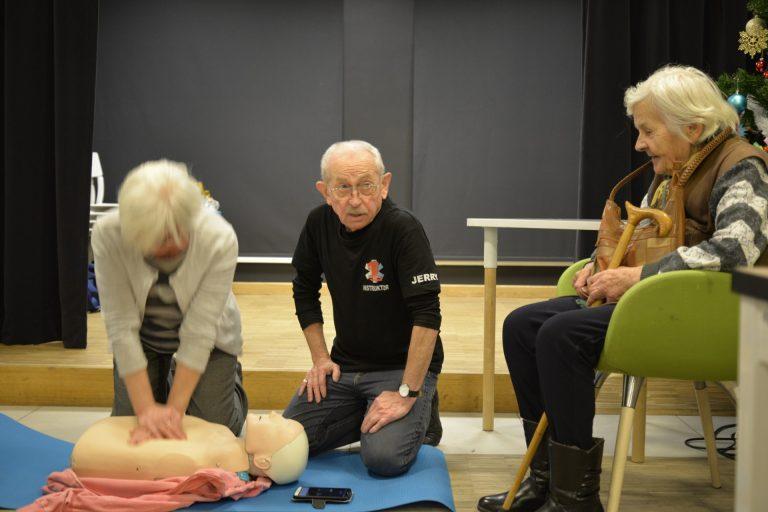 Jedna z uczestniczek spotkania ćwiczy na fantomie masaż serca na manekinie ułożonym na macie na podłodze. Obok niej siedzi instruktor i mówi. Po prawej na krześle siedzi starsza kobiueta, która trzyma w ręku kulę.