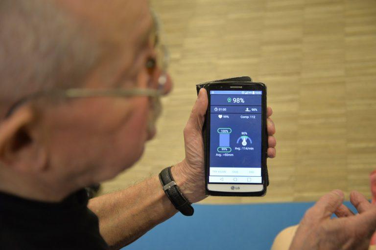 Snior trzyma w lewym ręku smartfon z otwartą aplikacją do pierwszej pomocy.