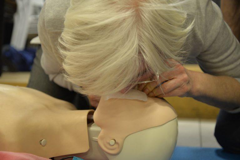 Starsza kobieta ćwiczy na fantomie sztuczne oddychanie.