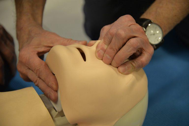 Na zdjęciu głowa fantoma - manekina szkoleniowego do pierwszej pomocy, trzymana przez instruktora w prawidłowym ułożeniu do sztucznego oddychania.