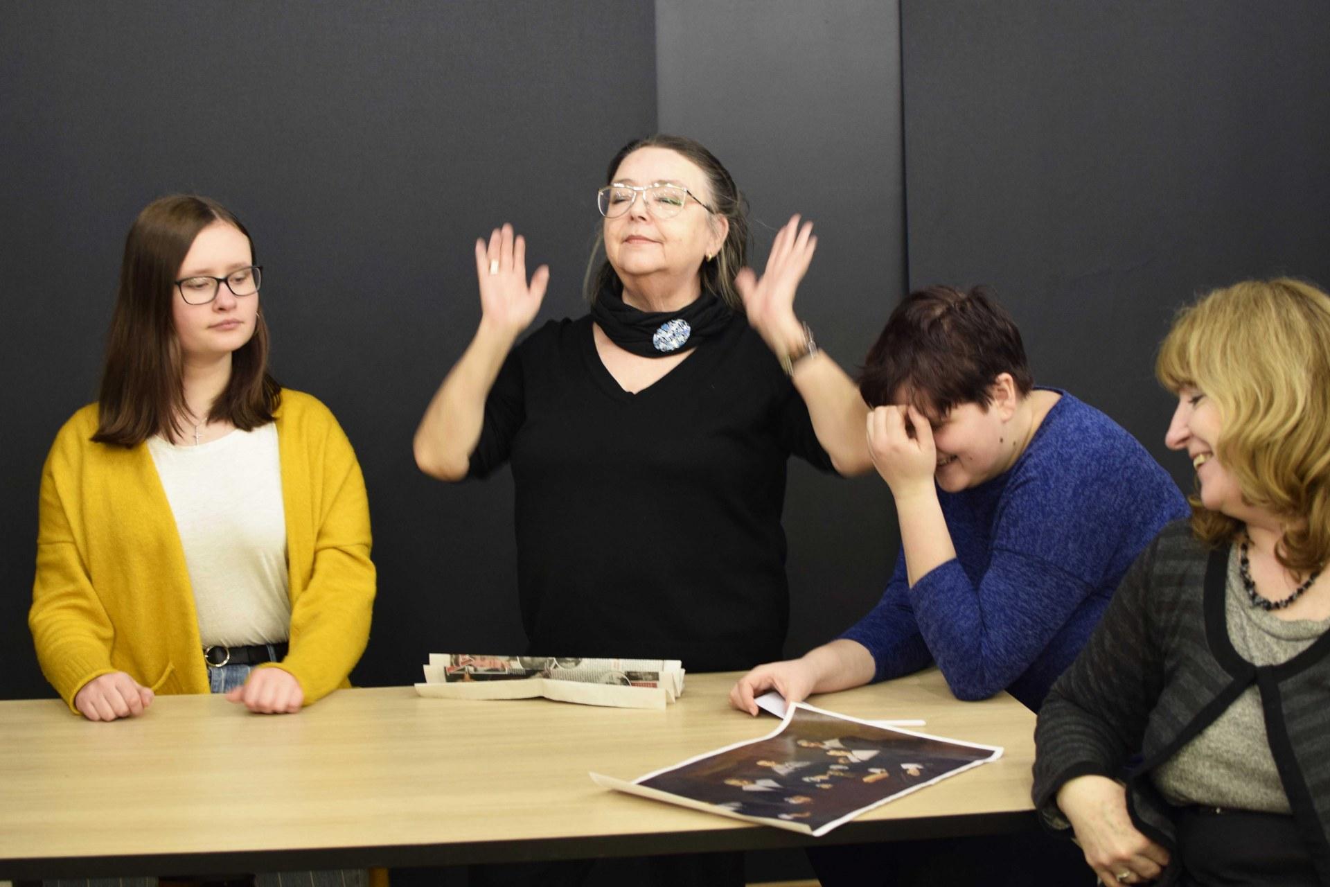 Na zdjęciu cztery kobiety w różnym wieku siedzą przy stole i dyskutują. Na stole leży reprodukcja obrazu Regentki Domu Starców, dzieło Fransa Halsa z 1664 r.