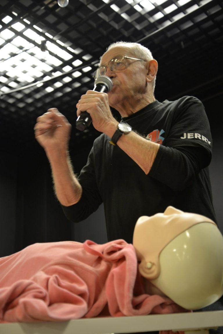 Na dole zdjęcia widać manekin - fantom do ćwiczeń masażu serca i sztucznego oddychania. Nad nim stoi instruktor - starszy mężczyzna mówiący przez mikrofon.