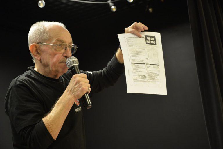 Instruktor stoi, mówi do mikrofonu, w lewej ręce trzyma wydrukowaną kartkę. U góry kartki jest napis Udar mózgu.