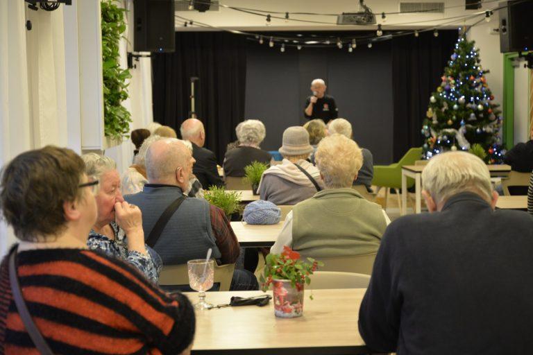 Prowadzący spotkanie stoi na końcu sali z mikrofonem i mówi. Przed nim siedzi kilkanaście osób starszych. Prowadzący stoi przodem do kamery na końcu sali, osoby słuchające wykładu siedzą tyłem do kamery.