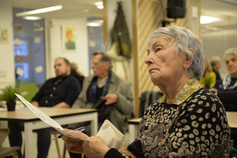 Na pierwszym planie siedzi starsza kobieta słuchająca wykładu, trzymająca w ręku kartkę i długopis. W tle widać niewyraźnie starsze, siedzące przy stolikach osoby.
