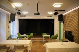 Pomieszczenie klubokawiarni, w głebi scena z kotarą przed nią stoliki i krzesła, widać rzutnik i kolumny