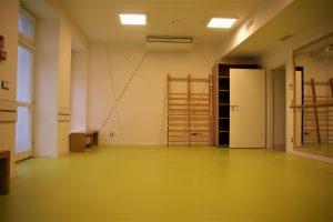 sala z wykłądziną na podłodze, drabinkami i lustrem oraz ławkami