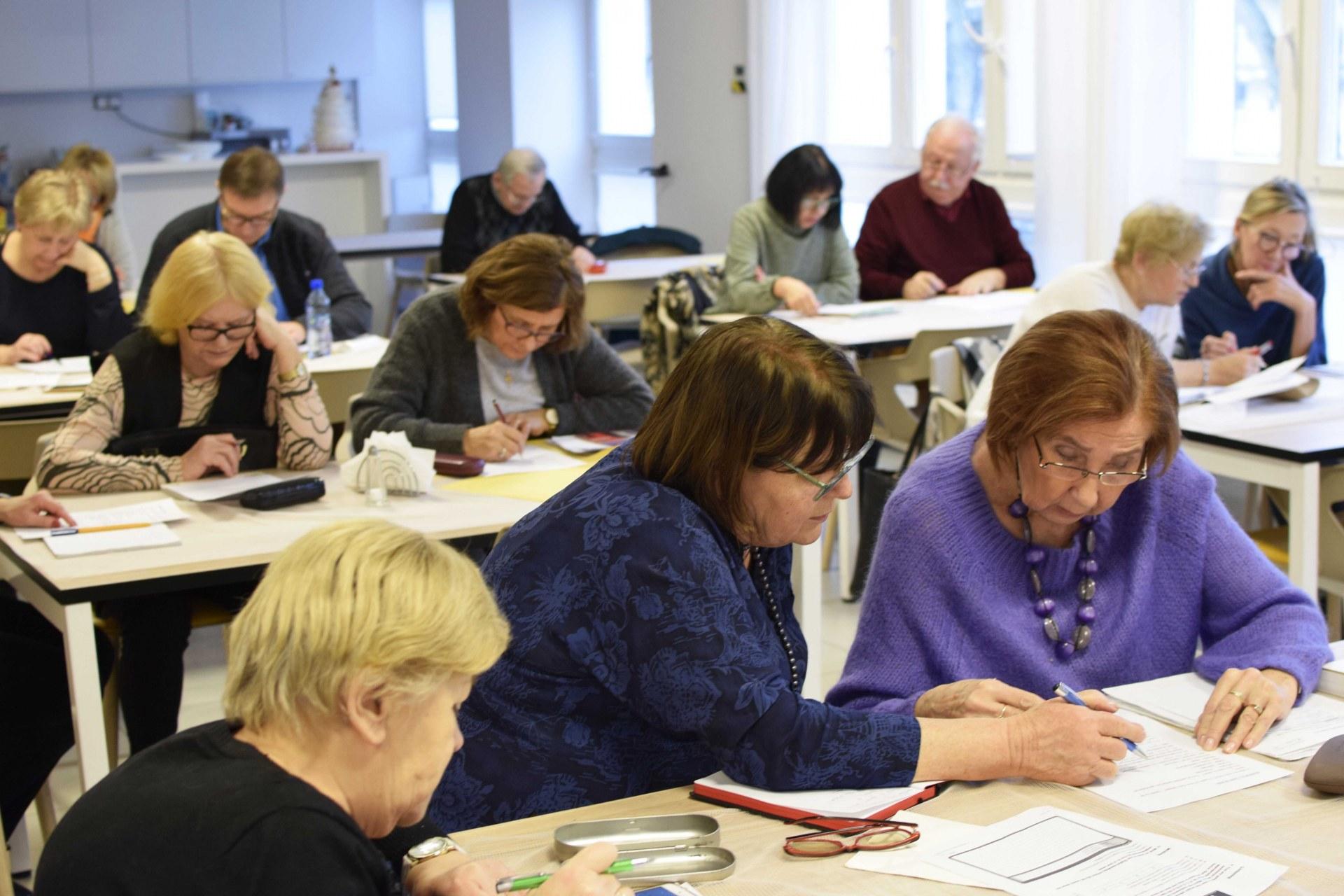 Zdjęcie z lekcji j. angielskiego. Na sali stoi kilka stolików, wokół których siedzą starsze osoby, głównie kobiety. Wszyscy uczestnicy zajęci są wypełnianiem testów.