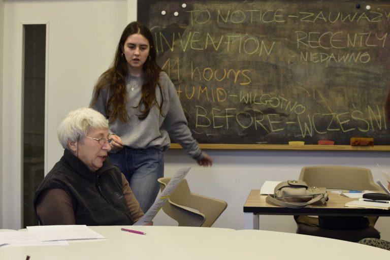 Na zdjeciu widać w tle tablicę, obok której, po lewej stronie stoi młoda kobieta z długimi włosami. Przed nią, przy stole siedzi starsza kobieta. Na tablicy różnokolorowymi kredami napisane są angielskie słowa.