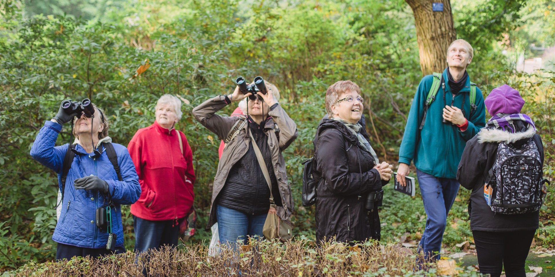 grupa sześciu osób w różnym wieku patrzy w górę, na tle zielonych drzew.