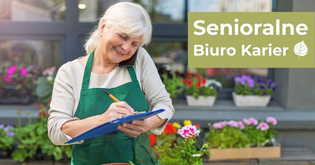 Starsza kobieta, ubrana w zielony fartuch, trzyma zeszyt i pisze, W prawym górnym rogu znajduje się napis na zielonym tle Senioralne Biuro Karier. Na dole strony widać skrzynki z kwiatami.