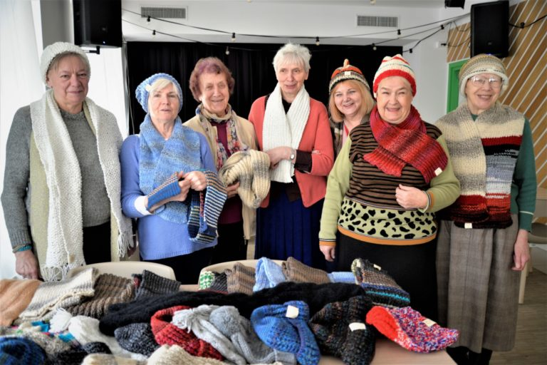 Siedem kobiet - uczestniczek grupy rękodzieła -pozuje do zdjęcia w zrobionych przez siebie czapkach i szalikach. Przed nimi na stole znajdują sie rozłożone prace: szaliki i czapki.