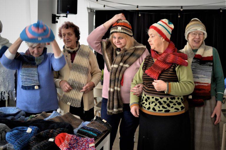 Trzy kobiety przymierzają czapki i szaliki.