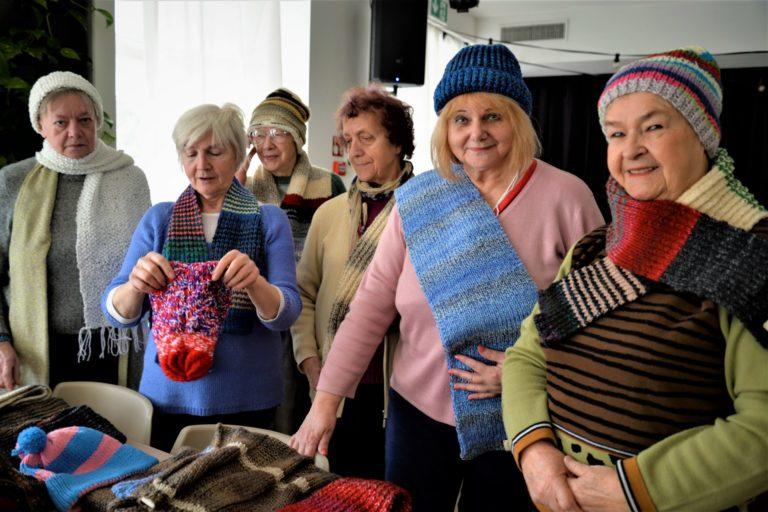 Kilka kobiet pozuje w zrobionych przez siebie szalikach i czapkach.