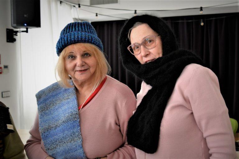 Dwie kobiety stoją obok siebie i pozują w zrobionych przez siebie czapkach i szalikach.