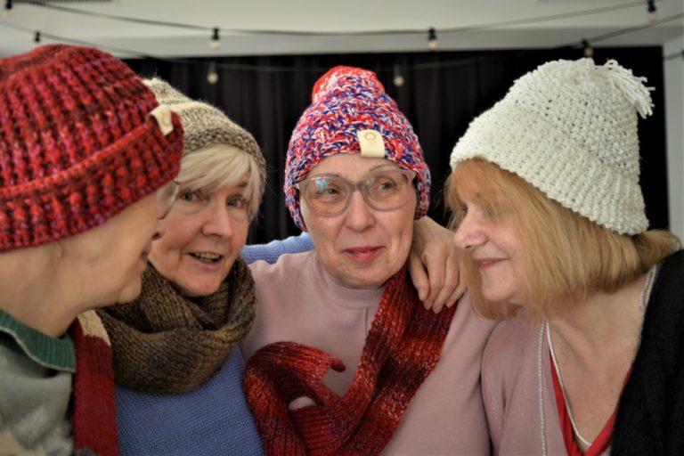 Cztery kobiety przytulone do siebie pozują w czapkach i szalikach.
