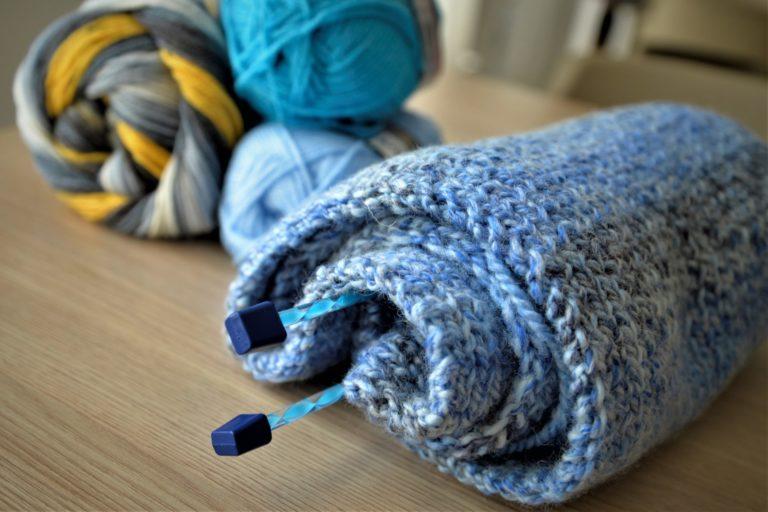Szalik w kolorze niebieskim zwinęty w rulon. Ze środka wystają druty. Wtle widać motki wełny w różnych odcieniach koloru niebieskiego i błękitu.
