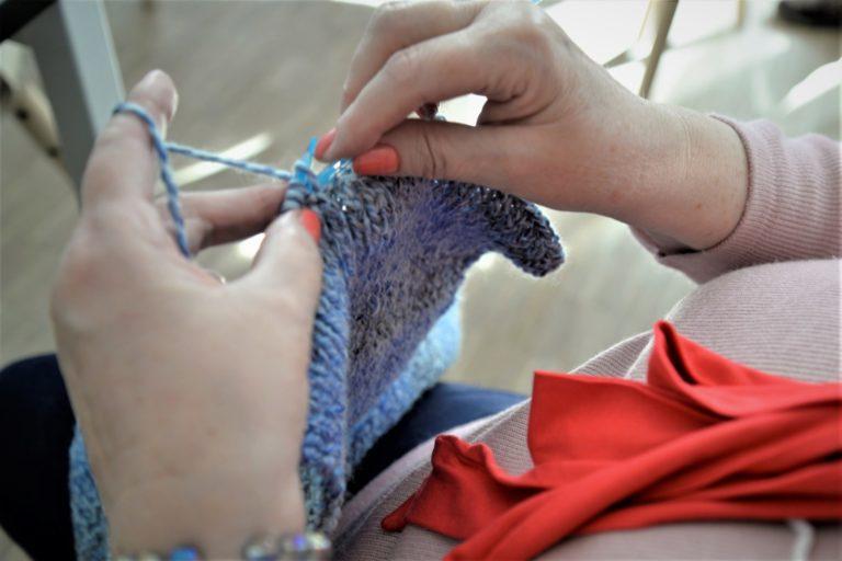 Zbliżenie na dwie kobiece dłonie trzymające druty, w trakicie robienia czapki lub szalika w kolorze niebieskim.