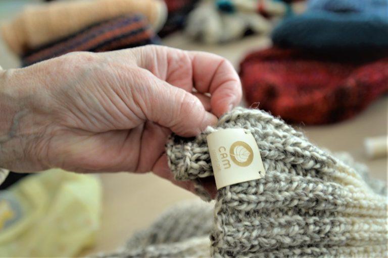 Na zdjeciu widać kobiecą rękę trzymającą szalik z naszywką z logotypem CAM Nowolipie.
