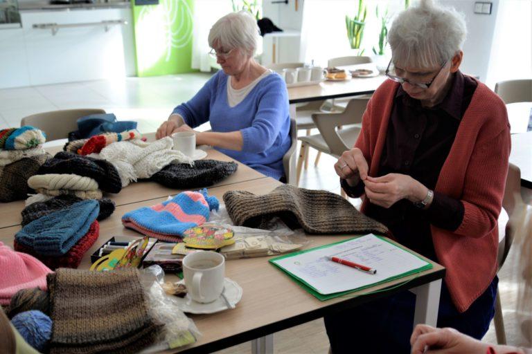 Dwie kobiety w wieku senioralnym siedzą przy stole na którym znajdują się narządzia rękodzielnicze: nożyczki, igły, wełna, oraz filiżanki. Kobiety robią na drutach i szyją.