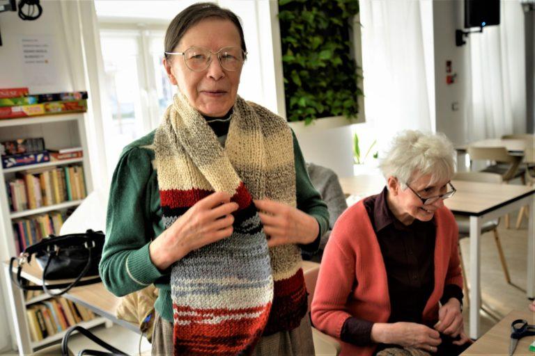 Seniorka pozuje w zrobionym przez siebie szaliku w beżowo-bordowo-błękitne pasy.