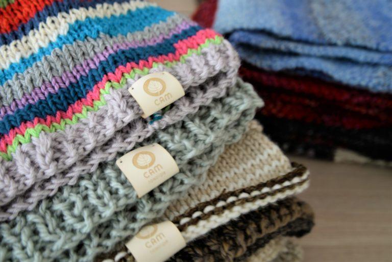 Czapki ułożone jedna na drugiej w róznych kolorach, dominują kolory beżowe i brązowe. Do każdej z czapek przyszyta jest naszywką z logotypem CAM Nowolipie.