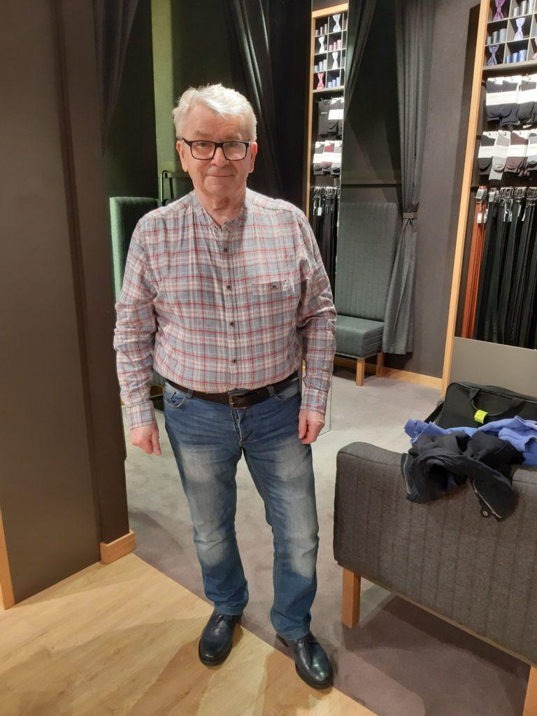 Senior w przymyeżalni sklepowej mierzy koszulę w kratkę i dżinsy.
