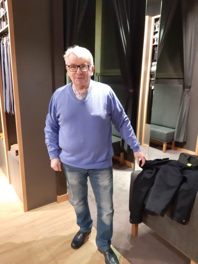 Senior w przebieralni sklepowej mierzy niebieski swetr.