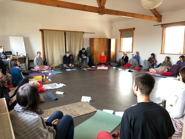 Uczestnicy sesji Mindfulness. Kilkanaście osób siedzi w dużej sali w okręgu na matach.