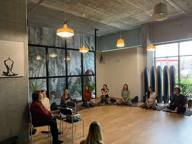 Uczestnicy sesji Mindfulness siedzą w okręgu na matach w dużej sali.
