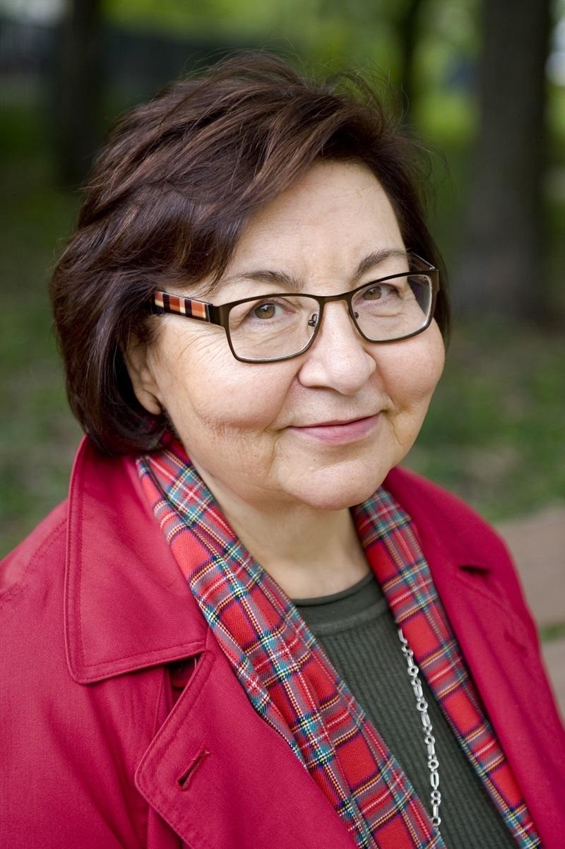 Portret uśmiechniętej kobiety w srednim wieku, ubranej w rózową marynarkę i szalik w czerwoną kratkę.