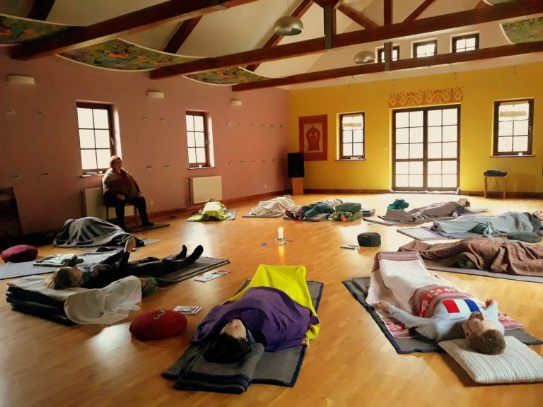 Sesja Mindfulness. W dużej sali na podłodze leżą na matach, przykryci kocami uczestnicy sesji.