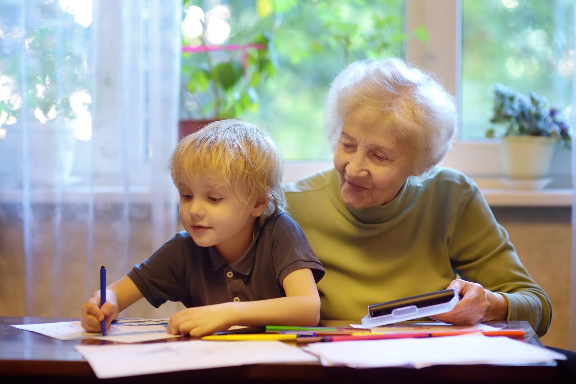 Babcia z kilkuletnim wnuczkiem na kolanach siedzi przy biurku.