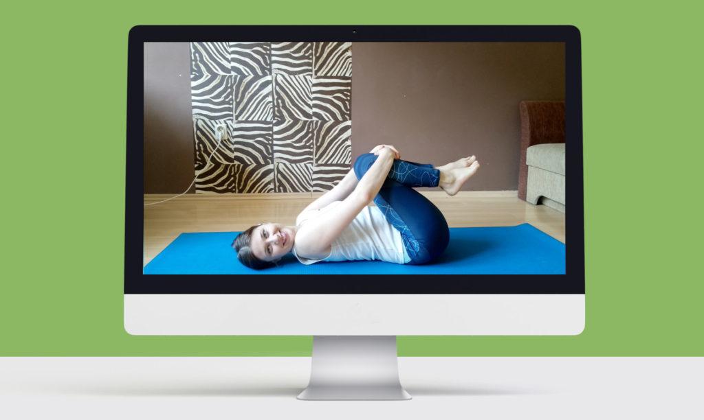 monitor komputera, na ekranie kobieta na macie do ćwiczeń lezy na plecach