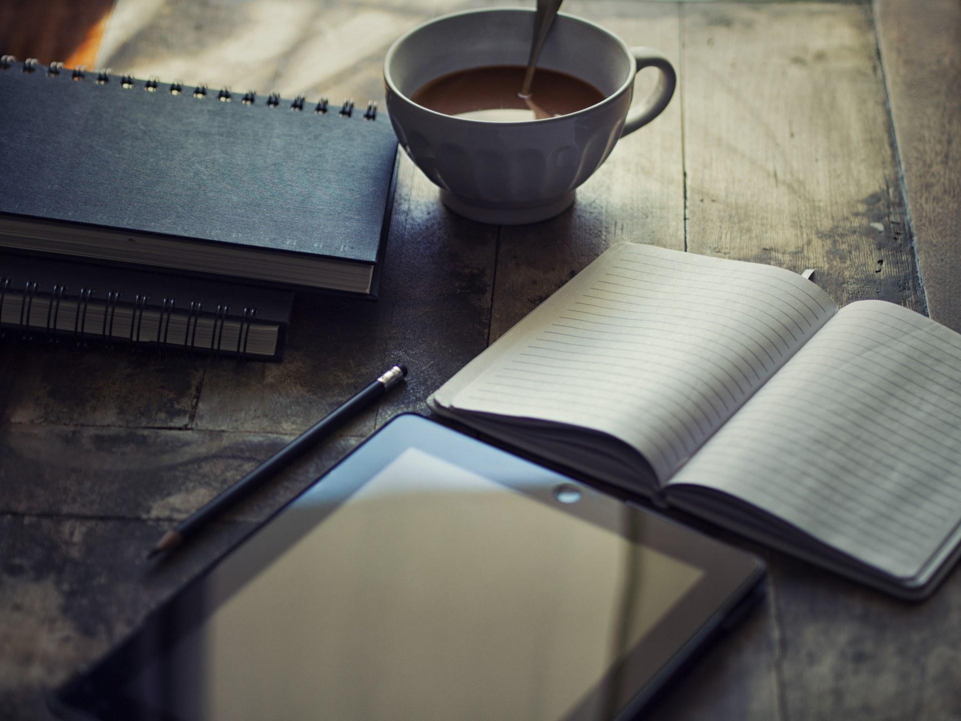 Na stole leży rozłożony zeszyt, obok niego stoi kawa, tablet, notoqatniki i leży ołówek.