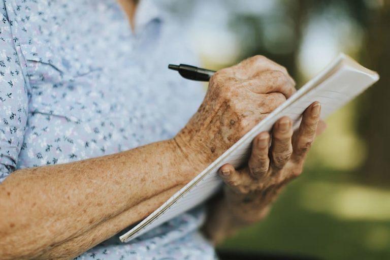 Kobieta w niebieskiej sukience trzyma notatnik i pisze długopisem.