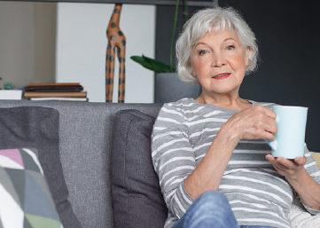 Seniorka siedzi na szarej kanapie, trzyma w ręku biały kubek.