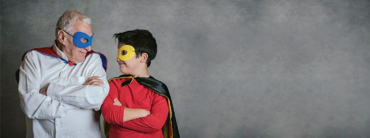 Po lewej stronie grafiki stoi senior i chopiec, patrzący na siebie. Na oczach mają maski a na ramionach peleryny.