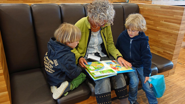 Starsza kobieta siedzi na kanapie z dwókją dzieci po każdej stronie. Na kolanach trzyma książkę z kolorowymi obrazkami.
