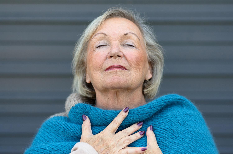 Kobieta nabierająca głęboki wdech, ma zamknięte oczy oraz ręce położone na szalu na piersiach.