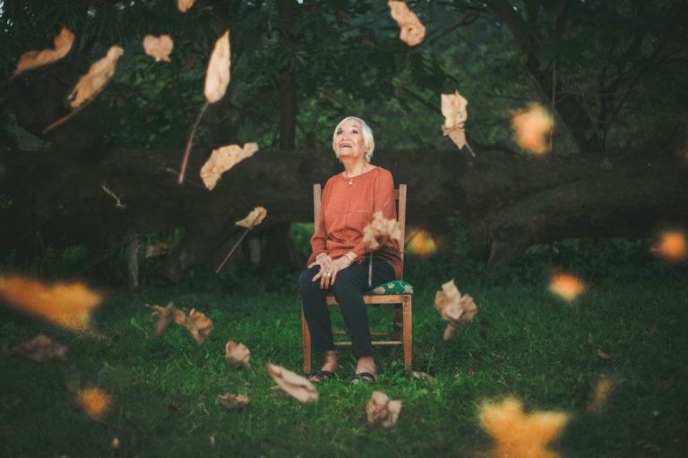 Starsza kobieta siedzi na krzesle. Wokół latają na wietrze suchw liście.
